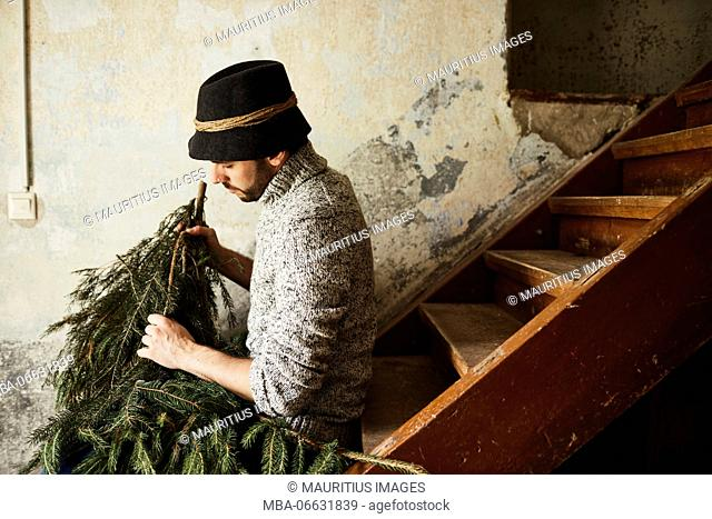 Man with knitted pullover and hat, twigs of evergreens for decoration, stairs, sit, sitting, half-portrait, side view