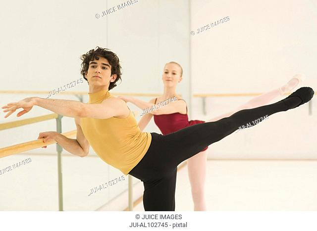 A ballet teacher and student practicing a position together