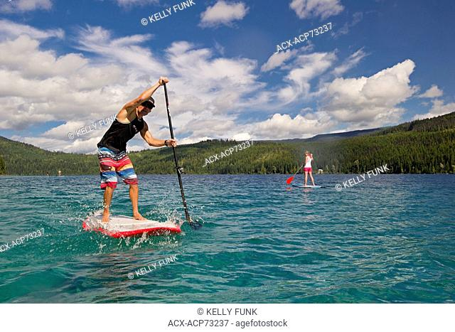 A professional paddle boarder makes his way across the tropical waters of Johnson Lake, North of Kamloops in the Thompson Okanagan region of British Columbia