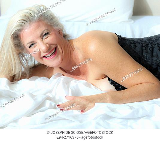 A sexy and pretty partially nude 52 year old blond woman on a bed smiling at the camera