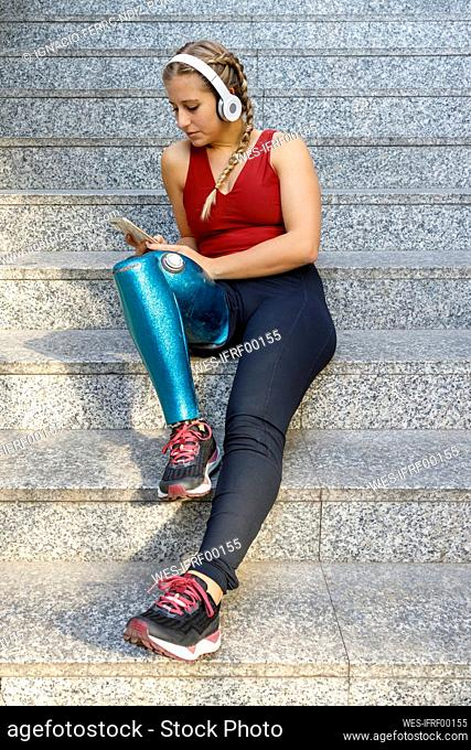 Young sportswoman with prosthetic leg using mobile phone while listening music sitting on staircase