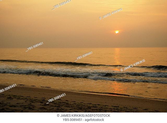The sun peaks through a haazy sky at the beach