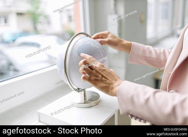 Businesswoman touching globe in office