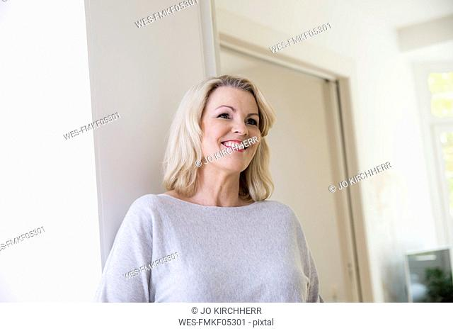 Portrait of smiling blond mature woman at home