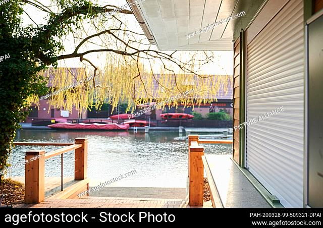 28 March 2020, Brandenburg, Lübben: The roller shutter of the bistro in Lübben is closed. On a sunny spring Saturday like today the terrace in the Spreewald...