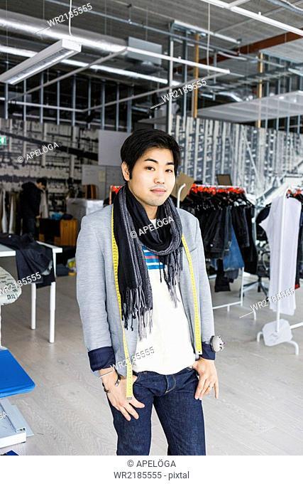 Portrait of confident male fashion designer standing in factory