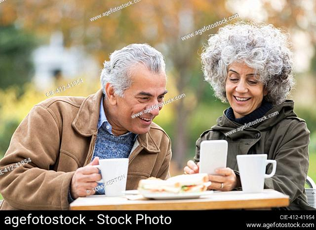 Senior couple with smart phone, eating lunch and drinking coffee in park