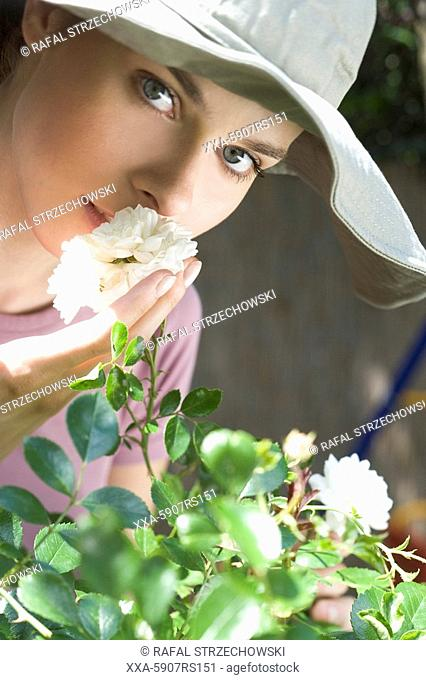 woman smelling white roses