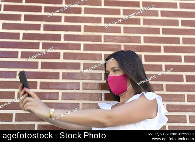 beautiful woman with pink mask taking a selfie from her smartphone