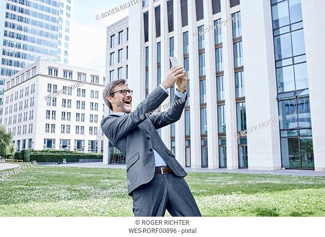 Playful mature businessman taking a selfie