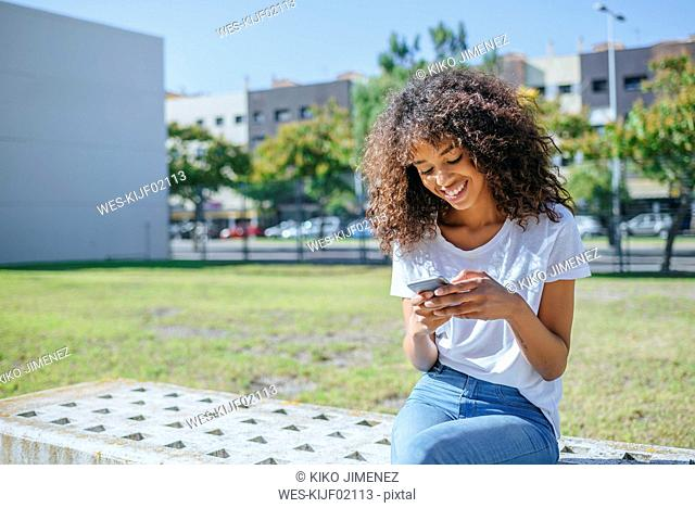 Smiling young woman sitting on bench text messaging