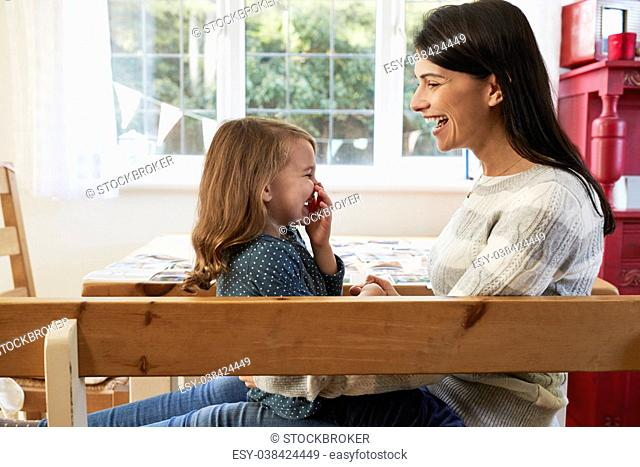 Daughter Sitting On Mother's Lap At Home And Laughing