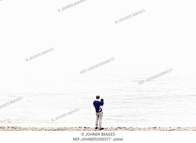 Man with child looking at sea