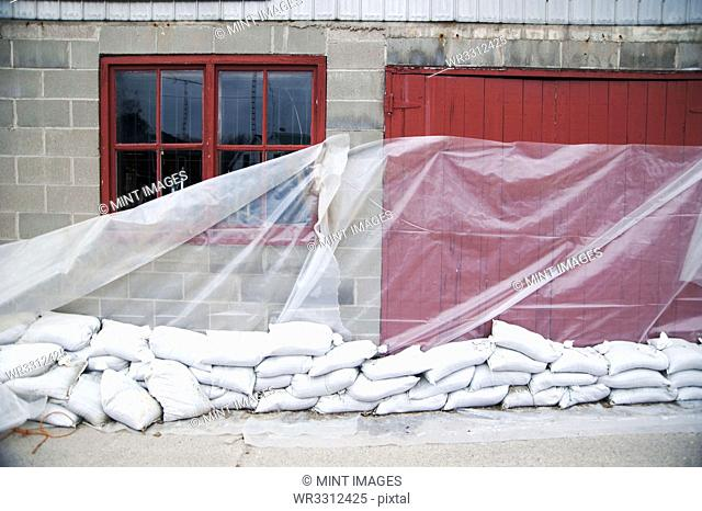 Sandbags and glass sheet on building wall