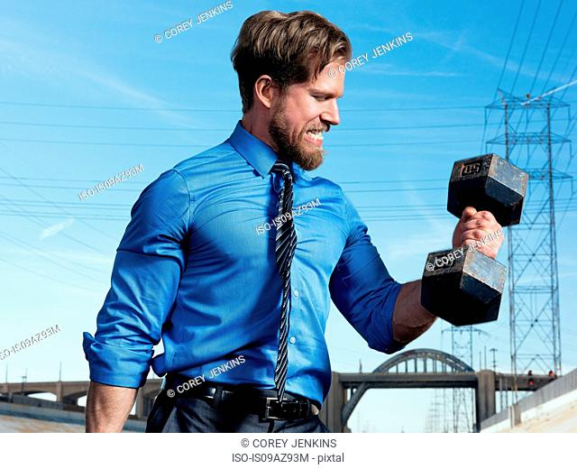 Businessman weightlifting, Los Angeles river, California, USA