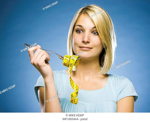 woman looking at a tape measure on a fork