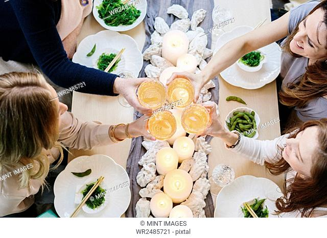 Overhead view of four people sharing a meal, plates of sushi and a table setting for a celebration meal