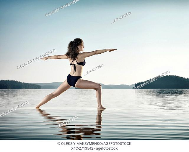 Young woman practicing Hatha yoga on a floating platform in water on the lake during sunrise in the morning over blue sky background