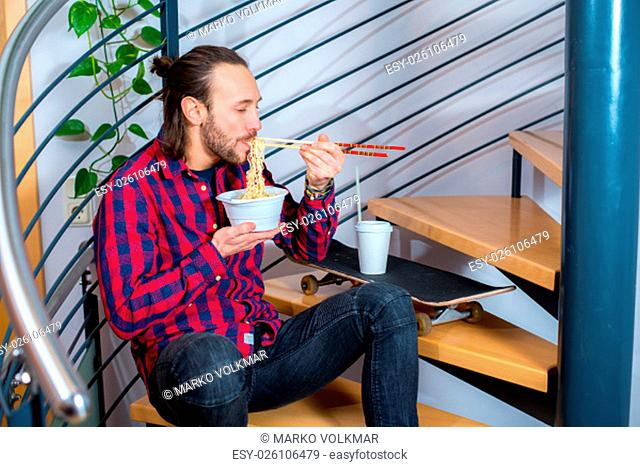 young man in checkered shirt sitting on stairs and eating asian food