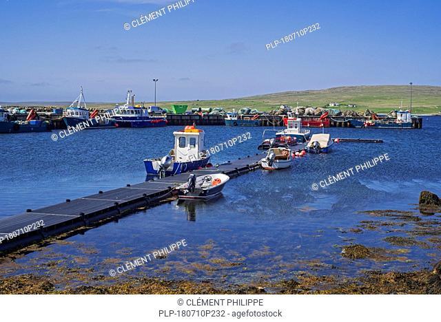 Fish farming workboats in the harbour of Uyeasound on the Isle of Unst, Shetland Islands, Scotland, UK
