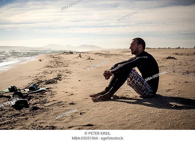 Kite surfer in Wet suit sitting on beach, thoughtful, wistful, beach, costa Brava, girona