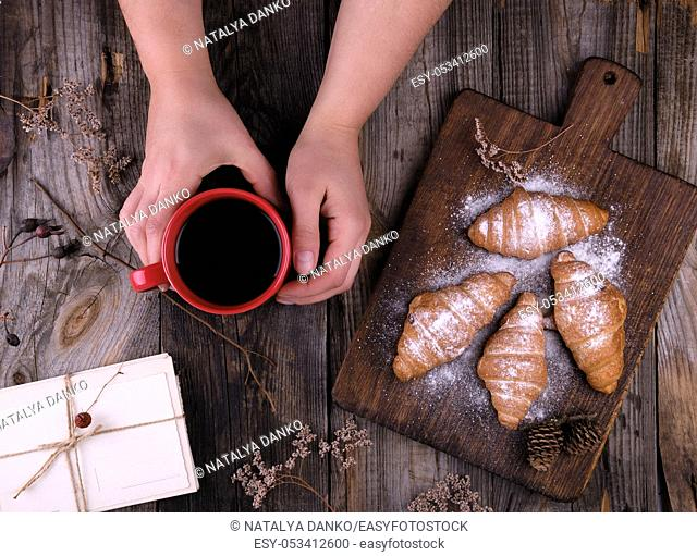 female hands holding a red ceramic cup with black coffee, next to baked croissants powdered with powdered sugar, gray wooden background, top view