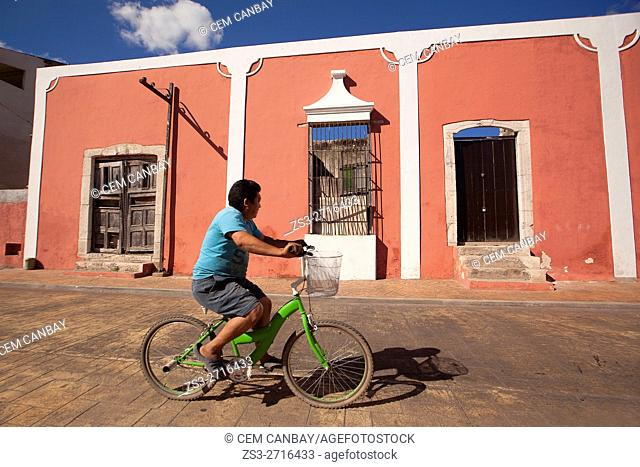 Man riding on a bike at the city center in front of colonial buildings, Valladolid, Yucatan Province, Mexico, Central America