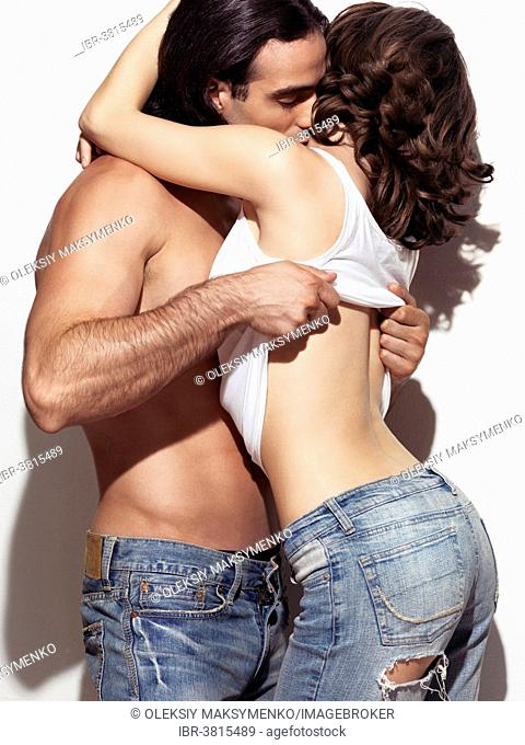Man with bare torso taking off woman's top