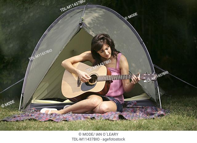 A dark haired girl sitting infront of a tent playing guitar