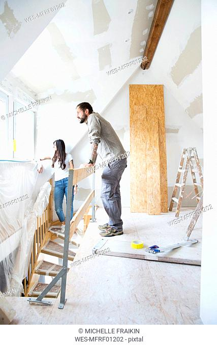 Couple in attic to be renovated looking out of window