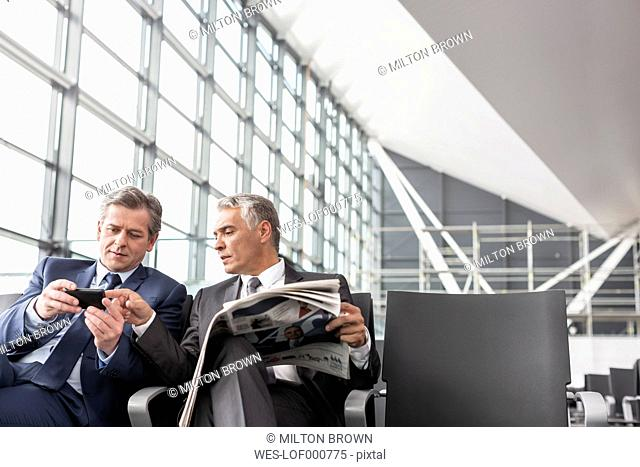 Two businessmen with cell phone and newspaper at airport departure lounge