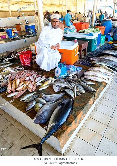 Merchant with various fish, fish market, Muttrah, Muscat, Oman