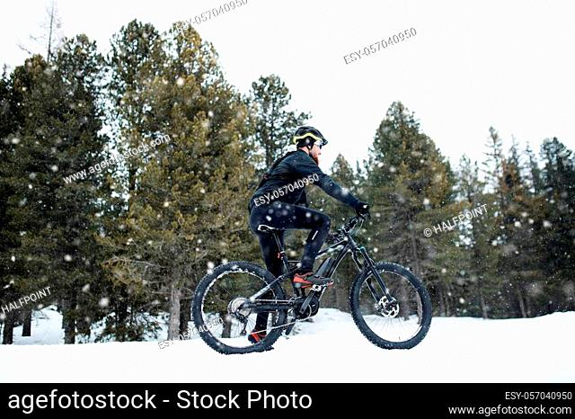 A side view of mountain biker riding in snow outdoors in winter nature