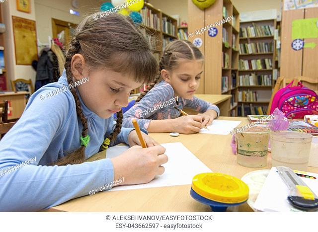 Schoolgirls in extracurricular activities draw in the library