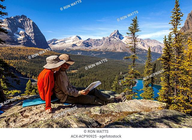 Two hikers on Opabin Prospect take a break overlooking Lake O'Hara in Yoho National Park, British Columbia, Canada. Model Released