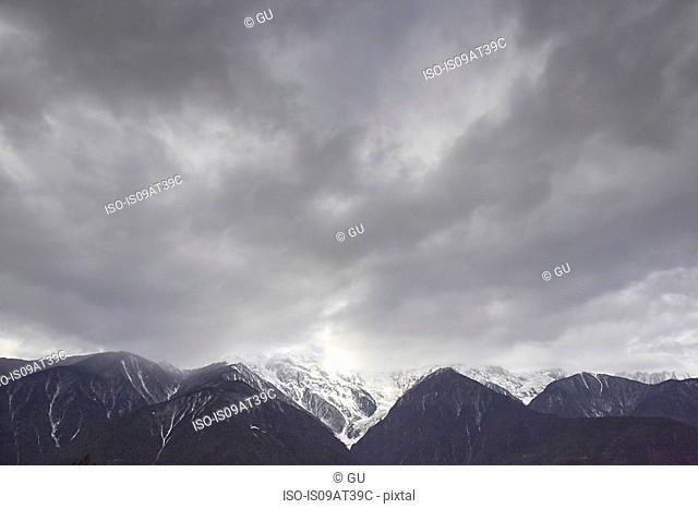 Dramatic cloudy sky and snow capped mountain range, Shangri-la County, Yunnan, China