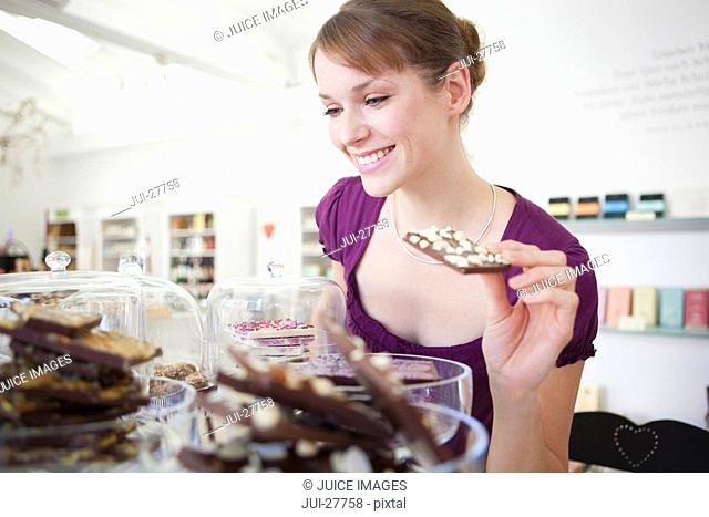 A woman choosing chocolate in a sweet shop