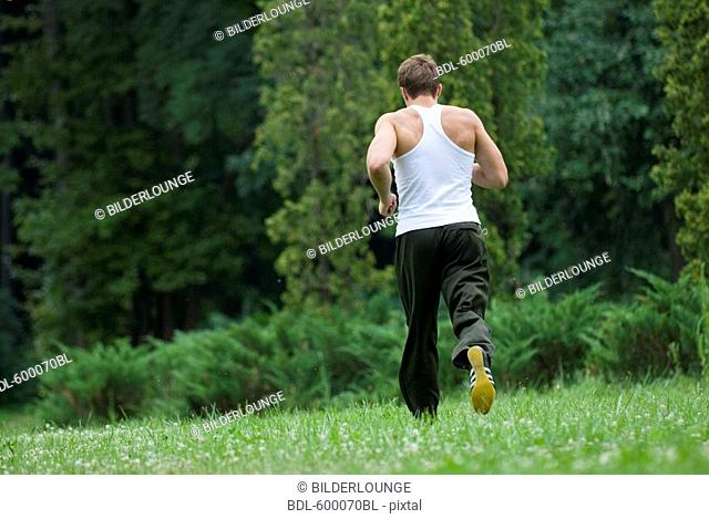 rear view of young man jogging through park