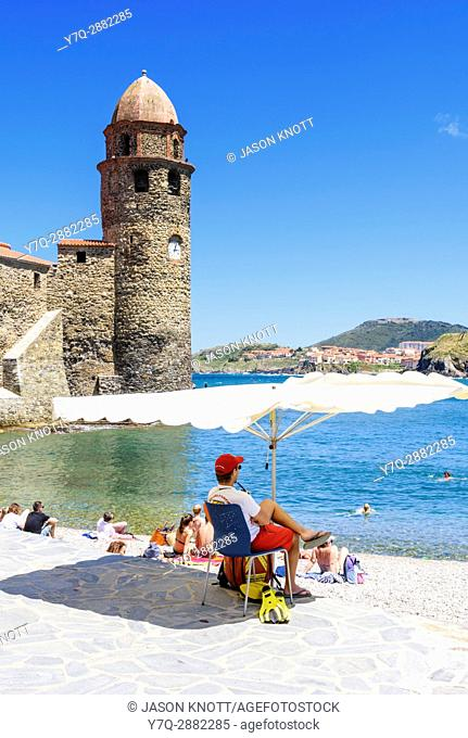 Beach lifeguard shaded by a beach umbrella on Plage Boramar near the tower of Notre Dame des Anges, Collioure, Côte Vermeille, Céret, Pyrénées-Orientales