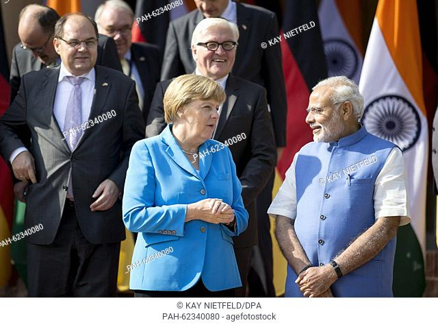 German chancellor Angela Merkel and Indian Prime Minister Narendra Modi speak as they pose on the stairs to the Hyderabad House for a group picture after the...