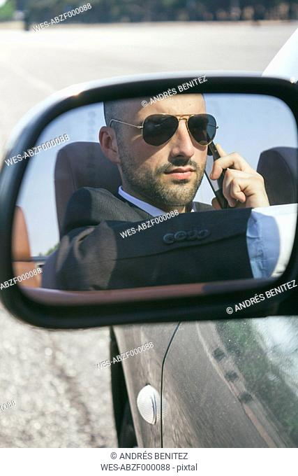 Mirror image of businessman with sunglasses telephoning in a car