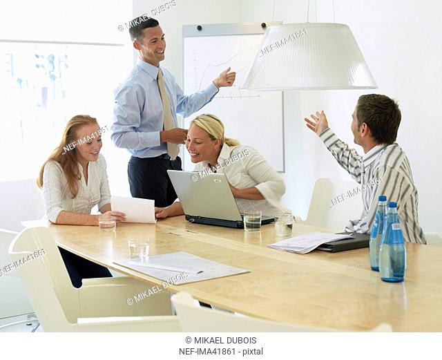 Two women and two men in an office having a meeting