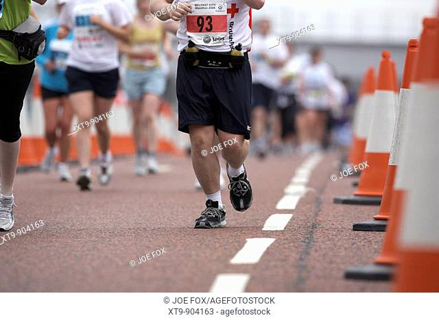 male competitor running along road beside cone lane markers during the belfast marathon 2008 belfast city centre northern ireland
