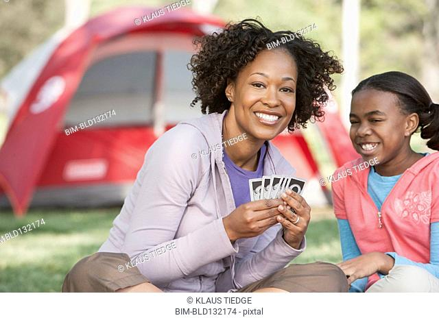 Mother and daughter playing cards at campsite