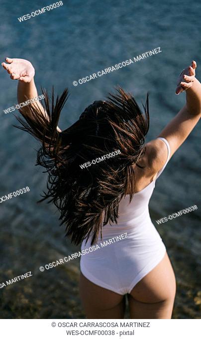 Back view of jumping woman at lake