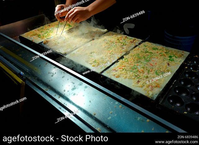 Takoyaki chefs prepare takoyaki for customers