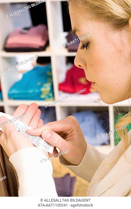 Young woman reading care instruction in a boutique