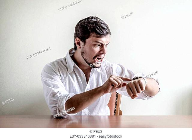 young stylish man with white shirt time wristwatch behind a table