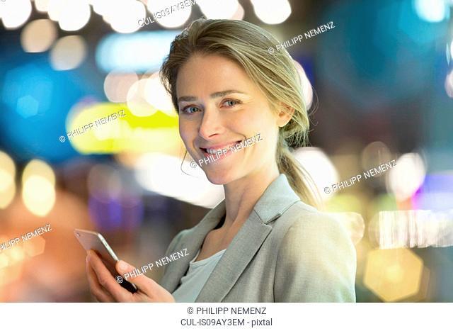 Portrait of businesswoman using smartphone on city street at night