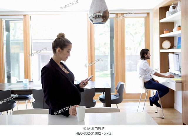Pregnant businesswoman drinking coffee and texting with cell phone in morning kitchen